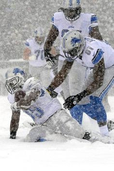 Calvin Johnson (WR) with ball in hand and snow in his helmet gets up with the help of Brandon Pettigrew (TE).  Pictured during the Lions-Eagles game on 12/8/13