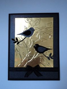 """By Candee. Dry emboss panel of brass sheeting in Cuttlebug """"Leafy Branch"""" folder. Adhere to black shimmery paper. Add ribbon with bow. Adhere to black card base. Die cut birds and branches from 2 kinds of black paper; interchange wings. Attach to card."""