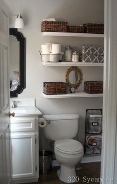 Small bathroom makeover - love the floating shelves and storage next to the toilet