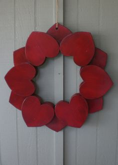 A WOOD WREATH OF RED HEARTS.