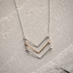 Freshie and Zero Triple Mini Chevron Necklace- Take the chevron down a notch with this mini chevron necklace by Freshie and Zero. Basically beautiful, three chevron stripes in silver and gold dangle from a dainty chain for just a touch of chevron style to your modern look.
