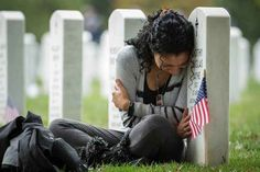 Thania Sayne leans on the headstone marking the grave of her husband, who was killed in Afghanistan in 2011, at Arlington National Cemetery. (Manuel Balce Ceneta / AP)