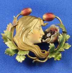 An Art Nouveau 14kt Gold and Enamel Brooch, attributed to Krementz & Co., depicting a woman entwined with poppy buds and blossom, old European-cut diamond accent.