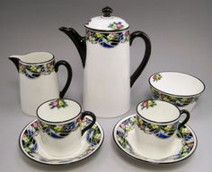 Doulton deco: unnamed coffee set by Robert Allen, H1651, RA9768, c1923 (pattern, backstamp). Yellow/pink colourway - geometric yellow and pink flower detail with black and blue highlights and black trim.