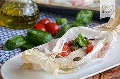 Branzino al cartoccio saporito, una proposta leggera per un secondo di pesce delicato e povero di grassi, con olive di Taggia, pomodorini, basilico.