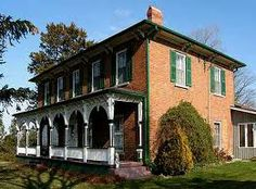 """Italianate: """"A rectangular 2-3 story house with wide eaves supported by large brackets, tall, thin first-floor windows, and the lower pitched roof that is topped with a cupola. Quoins (sometimes imitated in brick), pronounced cornices with paired brackets, and tall, narrow windows set under segmental arches."""""""