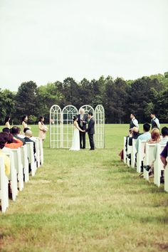 Old windows make a great backdrop for this outdoor ceremony.  Photo:  Photographs by Anjuli
