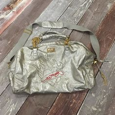 Ed Hardy metallic duffle bag GUC Ed Hardy metallic duffle bag. Inner pocket has some discoloration around the seam (see close up photo). Comes with wristlet. Ed Hardy Bags Travel Bags