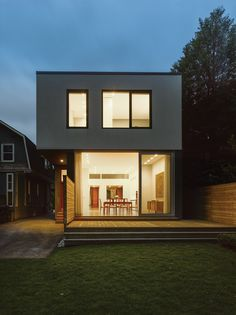 Light illuminates the back of the home at night. The Vicenza flamed basalt exterior and floor-to-ceiling windows are a bold counterpoint to the house's more traditional neighbors.