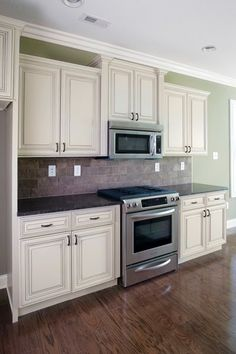 Explore color combo - dark floors, white cabinets, dark countertop, green walls...perhaps just need a mosaic back splash including greenish tones...