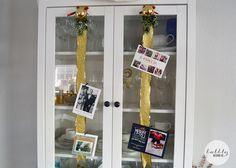 Use ribbon hung from a cabinet or curio to display holiday cards with mini clothespins