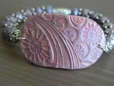 Stretch bracelet with a pink-purple polymer charm connector and purple glass beads