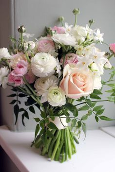 Pastel flowers in this spring time bouquet, pink and white ranunculus, paperwhites and peach roses