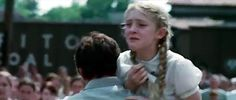 Primrose Everdeen being carried away;  Katniss sacrifices herself to save Prim.