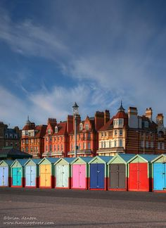 A stark contrast of building styles with de colorful beach huts on de promenade on Brighton & Hove seafront in East Sussex, England_ UK Brighton England, Brighton And Hove, Brighton Beach Uk, Brighton Rock, British Beaches, British Seaside, British Isles, Uk Beaches, United Kingdom