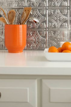 You can even cover a lackluster backsplash if you don't have the time (or money) to do any actual tile work. Three inexpensive options for this project are bead board, tin ceiling tiles or even a bunch of frames lined up next to each other. These materials can be attached with an adhesive or held up with removable products like 3M Command Strips, which are especially handy if you're a renter