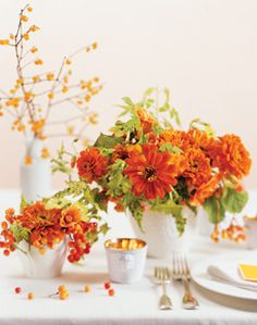 GARDEN-INSPIRED WEDDING FLOWERS   Wonderful old-fashioned favorites, zinnias bring pure joy to the table. This centerpiece has a natural charm that's ideal for a family wedding in the country. Zinnias are paired with orange abutilon (flowering maple), chartreuse nicotiana, acid-green jasmine, and two kinds of berries: orange-and-yellow viburnum and, in the background, berries from a honeysuckle bush.  White-glazed porcelain pots and gold-interior votive holder,