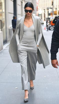 Kendall Jenner in a monochrome gray look: long-sleeve tee, wide-leg pants, pumps, and cape-jacket - click through for more fall outfits from celebrities