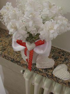 ciao a tutti.questo vaso di fiori l ho creato con stoffa,perline e cuoricino stampato in ceramica.per abbellirlo ho aggiunto un fiocco di raso