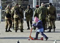 Feb. 23, 2015 photo, a child plays near Russia-backed separatists in Donetsk, Ukraine