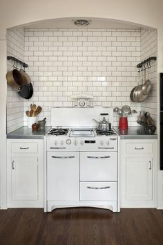 Love the stove in the alcove with hanging pot storage on either side.  Brilliant for my tiny kitchen with its overabundance of pots and pans.