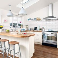 Small kitchen with white splashback tiles, wooden floor, white cabinetry, white kitchen island and wood worktops
