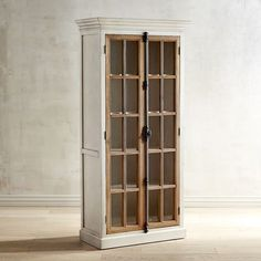 """Originating in 19th century Europe, the """"Cremone bolt"""" is a traditional casement-window locking device with a latch/handle mechanism. Featured on all our hand-hewn Cremone cabinetry, it's as beautiful as it is functional. Also featured: Antique white wood frames with protracted crown molding, contrasting natural wood casements and tempered pane-glass windows. Our tall cabinet houses four adjustable shelves."""