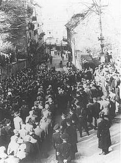 """After the Kristallnacht (""""Night of the Broken Glass"""") pogrom, German civilians line the streets to watch the forced march of Jewish men thro..."""