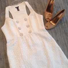 "NWT White Dress Gorgeous, white dress that I have never wore!  White and gold button details on the chest and a razor back cut on top to show off your shoulders!  The dress is about 36"" from shoulder strap to bottom hem.  The dress is a cotton and polyester mix and is completely lined. The dress even has pockets!  What's better than a dress with pockets!?! New Directions Dresses Mini"