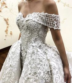 This haute couture wedding gown has an off the shoulder neck line. The ornate ball gown skirt is a fashion statement. The beading & embroidery lace detail are wonderful. Custom wedding dresses like this do not have to cost a ton of money. We can make #replicas of haute couture designer dresses for an affordable price. So if your dream dress is out of price range email us a picture for pricing of a replica.