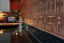 Embossed wallpaper backsplash painted to imitate copper.