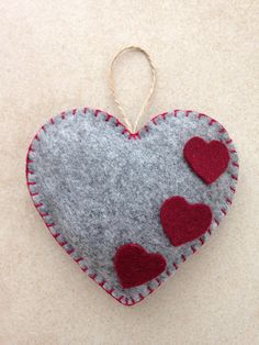 Items similar to Felt Heart Ornament, handmade on Etsy Saint Valentines day handmade hanging felt ornament. Colour: grey on the front and bourdeaux on the back. Decorated with three little bourdeaux felt hearts. Size: about x Valentines Bricolage, Valentine Day Crafts, Xmas Crafts, Felt Christmas Decorations, Felt Christmas Ornaments, Etsy Christmas, Fabric Hearts, Felt Embroidery, Heart Crafts