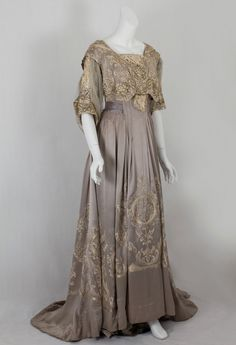 Made from dove gray silk charmeuse with matching chiffon sleeves, this exemplar of the Callot style is lavishly hand embroidered with silk floss and subtle gold metallic thread. The lace inserts on the bodice front tab and neckline and on sleeves are of handmade Venetian lace. The woven label on the petersham reads Callot Soeurs/Paris/Hiver 1905.