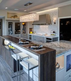 Stone countertop on the large island here is wrapped in an oak dining bar, beneath a shimmering box-style chandelier.Range stands on marble countertop with matching backsplash, while glass cabinets at left feature built in wine cooler.