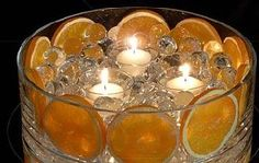 This is great for a night time summer party. Use orange slices, clear beads, and place candles into simple holders.