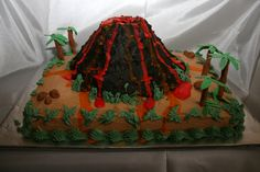 Volcano cake - Triple choc sheet cake with buttercream. Volcano made of RKC sealed with royal icing and iced with butter cream. Palm trees made with fondant wrapped around sucker stick, leaves also fondant. Rocks made of fondant. Lava flows yellow and red with color flow.