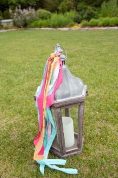 Adding ribbon to big lanterns to incorporate colors