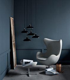 """Paynesgrau ist ein blaustichiges, dunkles Grau. Der intensive Farbton ist sehr präsent und bringt Ruhe - ideal für eine gemütliche Leseecke, hier mit dem Sitzklassiker """"Egg Chair"""" und Ottoman. Damit das Arrangement nicht zu düster wird, wurde der Sessel mit einem hellgrauen Stoff bezogen. Accessoires aus Holz dienen als Kontrast."""