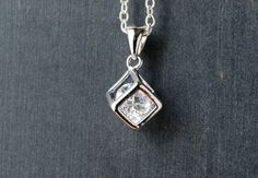Silver plated cube pendant with cubic zirconia gemstone accent. This little silver plated cube pendant features an open design used to showcase a