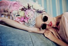Modern take on Marie Antoinette's style, a Wildfox model wears 18th century inspired sunglasses with hair piled high in a pouf and lays on a blue velvet couch
