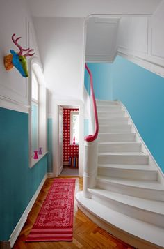 Colorful hall stairway with white & aqua walls and red rug, handrail, and wallpaper accents