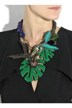 Gold-tone brass chain-link necklace with muticolored glass stone and Swarovski crystal bird of paradise embellishment. Lanvin necklace has an inter-woven brown ribbon, purple acetate beads, two green cutout acetate leaf charms, a glass and crystal flower detail, a clasp to fasten to neck and comes in a signature blue designer-stamped box.