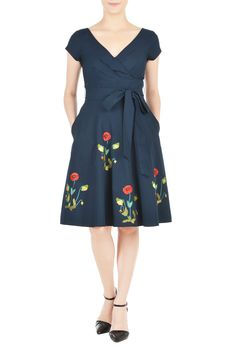 A wide V-neck lends alluring sophistication to our cotton poplin dress embellished with colorful florals at the full flare skirt and cinched in with a sash tie belt at the wide banded empire waist.