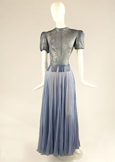 Lilac Lame and Chiffon Gown   American, 1940s   The bodice of lame, sewn to castellate at waist to top of hip, short padded sleeves, single self button and loop at round neckline, slash to cleavage, self buttons to below waist, the paneled skirt of gathered chiffon