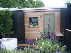 This funky little garden room has it all. Including a shed attachment with covered canopy & integral seating. Clever!