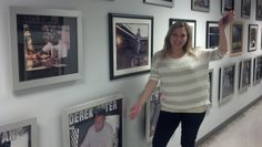 Director of Talent Services Erica Marrero stands by the Wall Of Fame at the Steiner Sports Warehouse