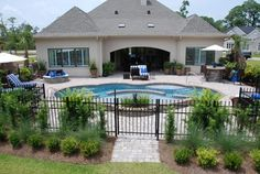 Trilogy Fusion Gemini (16 x 32) with Tanning Ledge fiberglass swimming pool done in River Rock Hydrostone finish. Brick coping with Belguard pavers and two tone tiles. 2 spillovers and fountain. Photo: Raleigh Unseen Photography (Cameron Purser)