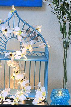 Mais um exemplo da gaiola que vira luminária: basta preencher a peça com aqueles pisca-piscas de Natal e pronto. Aqui, as luzinhas vêm disfarçadas de orquídeas
