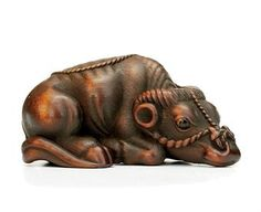 A Wood Netsuke With signature Tomotada, Edo-Meiji Period (19th century) Of a recumbent ox 6.6cm. wide