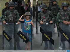 """THAILAND, Bangkok: A boy poses for a photograph with Thai soldiers at Victory Monument, the site of recent anti-coup protests which has been sealed off by security forces to prevent further rallies on May 30, 2014 in Bangkok. The European Union has voiced """"extreme concern"""" about political detentions and censorship in Thailand, as the military junta chief met officials and began to set out plans for the country's future. AFP PHOTO/ Nicolas ASFOURI"""